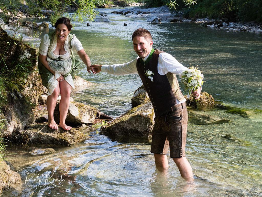 Brautpaar in Tracht im Wasser eines Gebirgsbaches